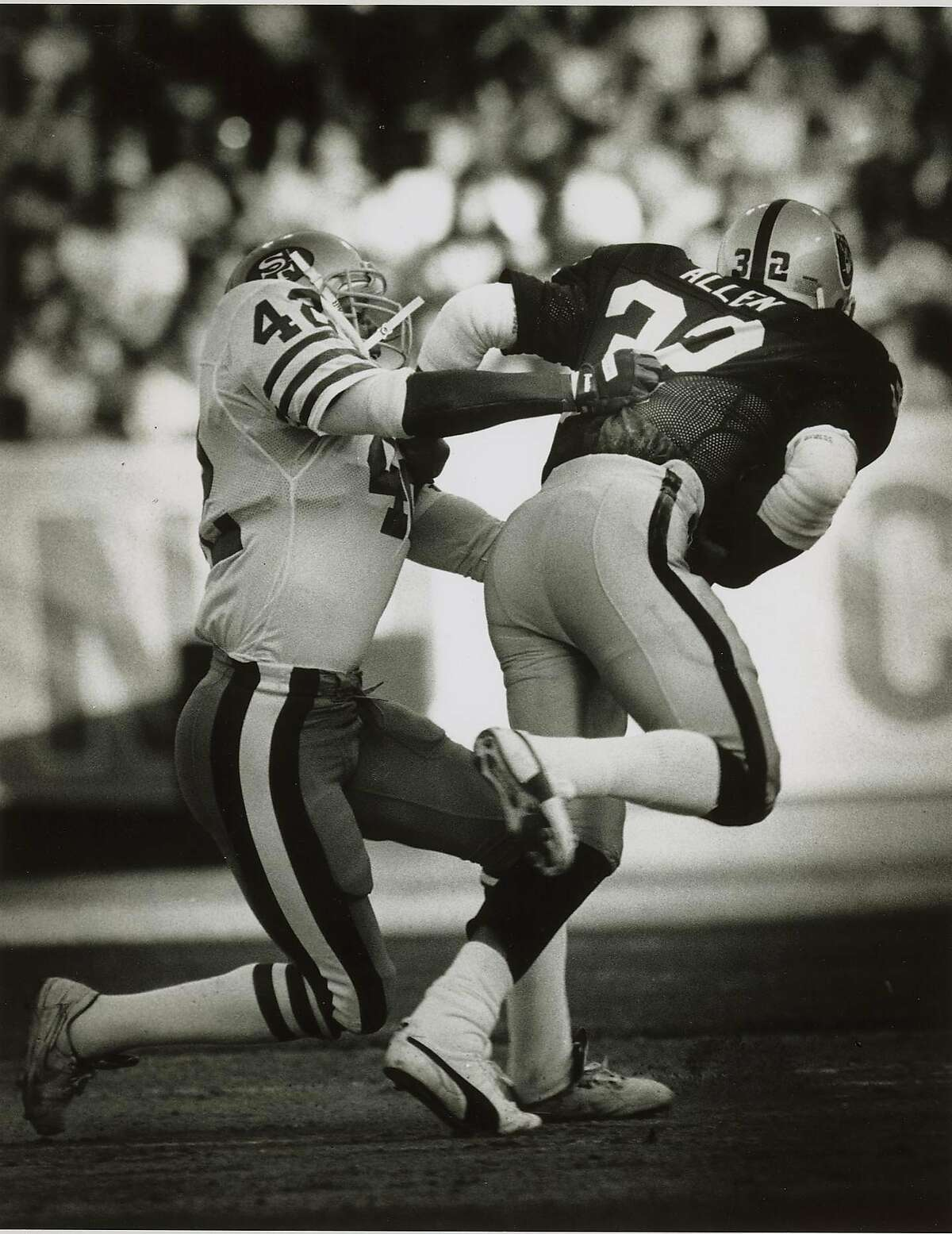 8/11/1990 - Ronnie Lott tackles Marcus Allen in the 1st quarter of game against Oakland Raiders.