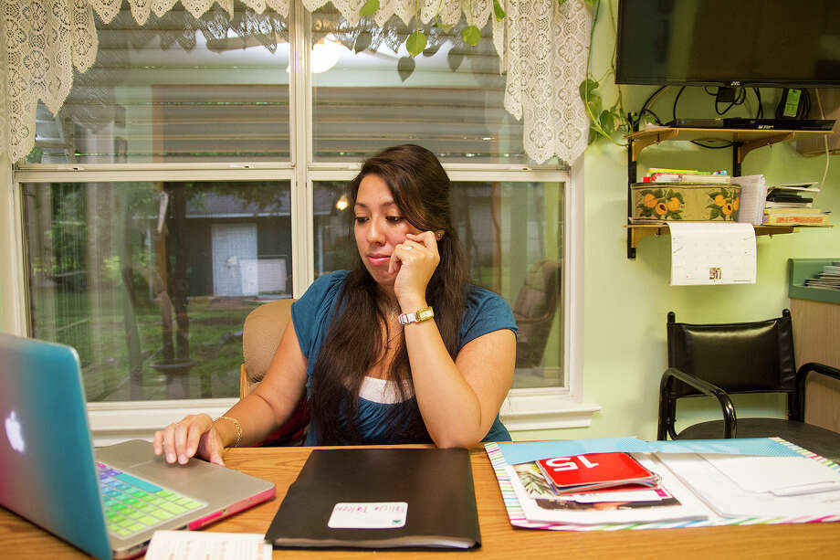 Felicia Falcon does some monthly budgeting at the kitchen table in her grandparents home, Friday, May 20, 2016. Photo: Alma E. Hernandez, For The San Antonio Express News / Alma E. Hernandez / For The San Antonio Express News