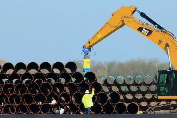 Workers move pipes last year for the proposed Dakota Access oil pipeline at a staging area in Worthing, S.D.