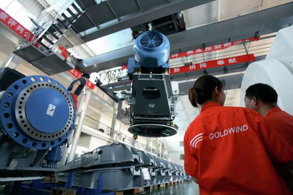 Workers assemble wind turbines at Goldwind Science & Technology Co. in Urumuqi, China. Goldwind is the largest maker of power-generating wind turbines in the world.