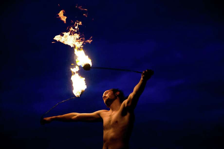 A flow artist performs with fire poi during the Golden Gardens Flow Art Gathering on Friday, May 20, 2016. Photo: GRANT HINDSLEY, SEATTLEPI.COM / SEATTLEPI.COM