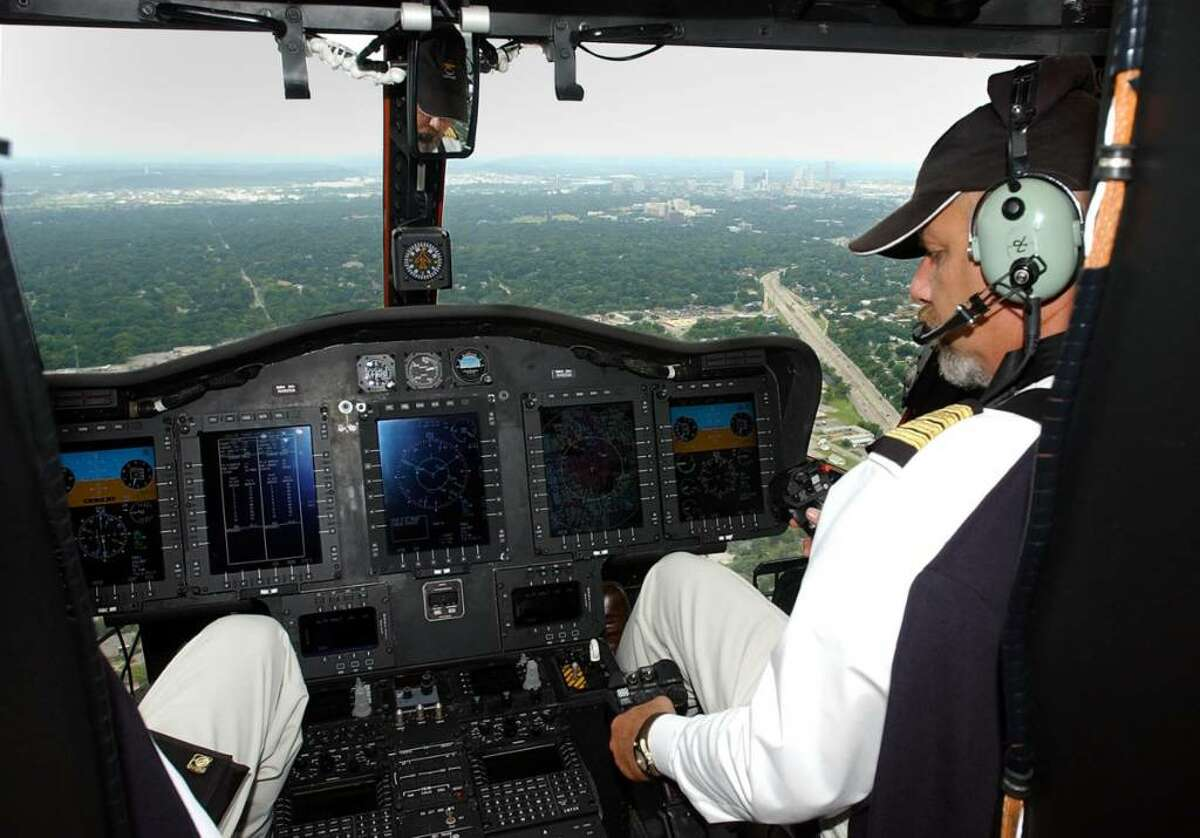 Pilot John Armbrust, right, sits in the cockpit of a prototype Sikorsky VH-92 helicopter as it flies over the Tulsa, Okla. in 2004.