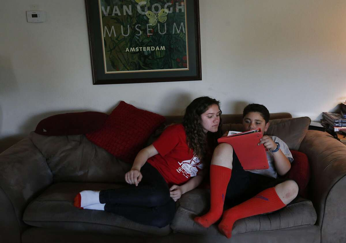 Lily, 11, left, helps her brother Luke, 10, with his homework after school in the Figueroa home May 20, 2016 in San Leandro, Calif.