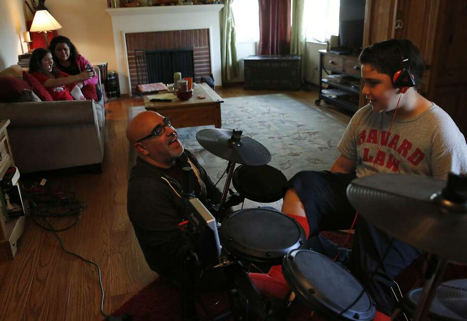 Orlando Figueroa helps son Luke, 10, with his drums while wife Heather and daughter Lily, 11, take a selfie on the couch. Figueroa bought a limited policy. Photo: Leah Millis, The Chronicle