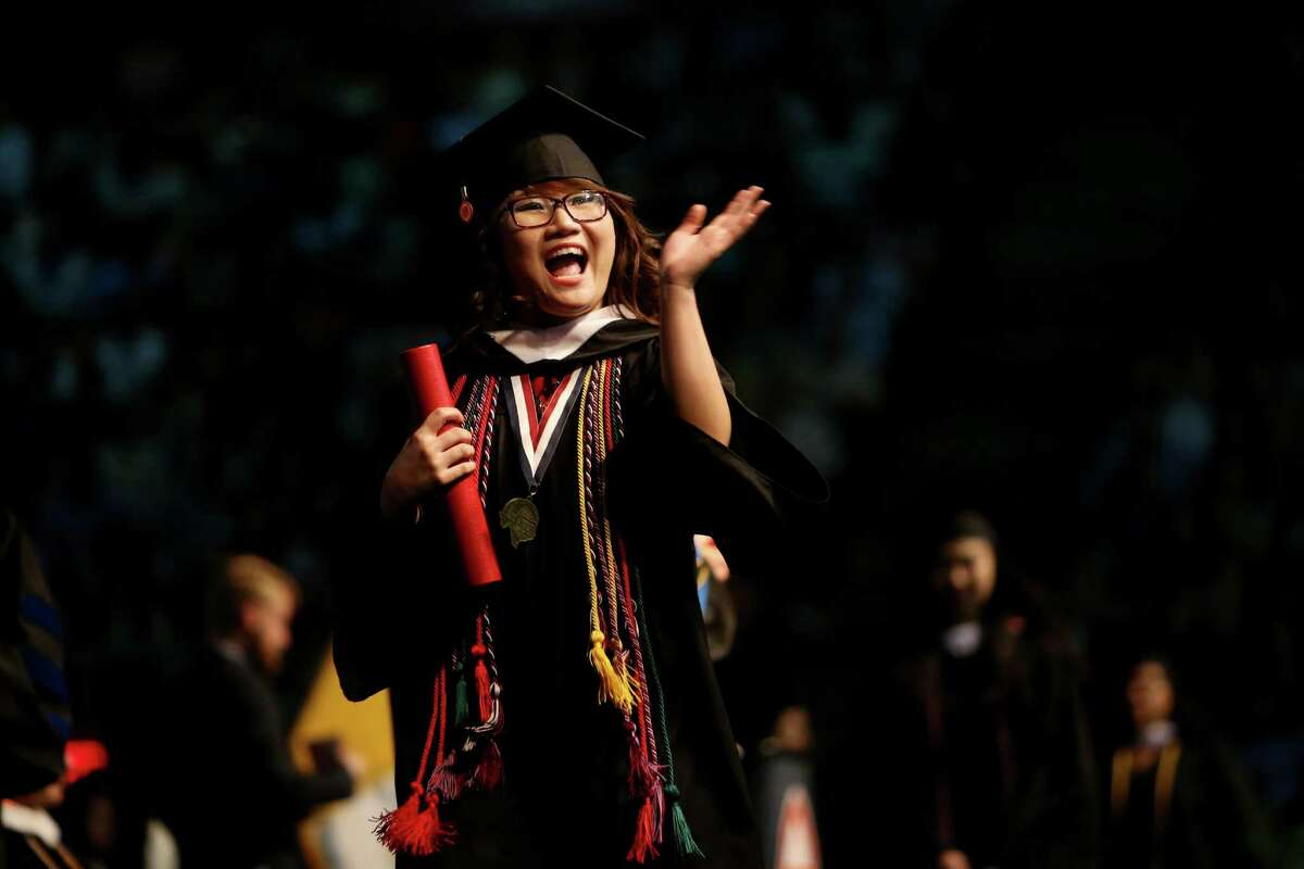 Nhi Nguyen waves to family after receiving a bachelor of arts at the University of St. Thomas Spring Commencement held at NRG Arena, Saturday, May 21, 2016, in Houston, Texas. Gov. Greg Abbott delivered the commencement address and was awarded an honorary Doctor of Letters degree.