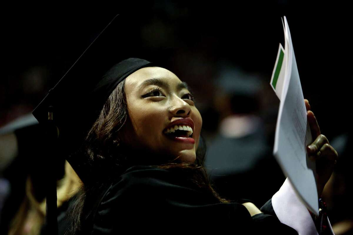 Thinh Nguyen waves to family before receiving a bachelor of arts in education at the University of St. Thomas Spring Commencement held at NRG Arena, Saturday, May 21, 2016, in Houston, Texas. Gov. Greg Abbott delivered the commencement address and was awarded an honorary Doctor of Letters degree.
