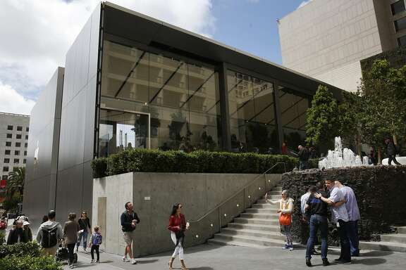 People walk past the back of the new Apple store during its grand opening on Post and Stockton streets in Union Square May 21, 2016 in San Francisco, Calif.