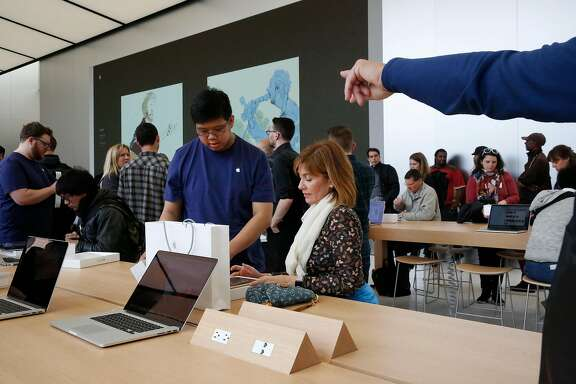Apple employee Brent Lam, left, helps Renata Saboia set up her new iPad Pro during the opening of the new Apple store on Post and Stockton streets in Union Square May 21, 2016 in San Francisco, Calif.