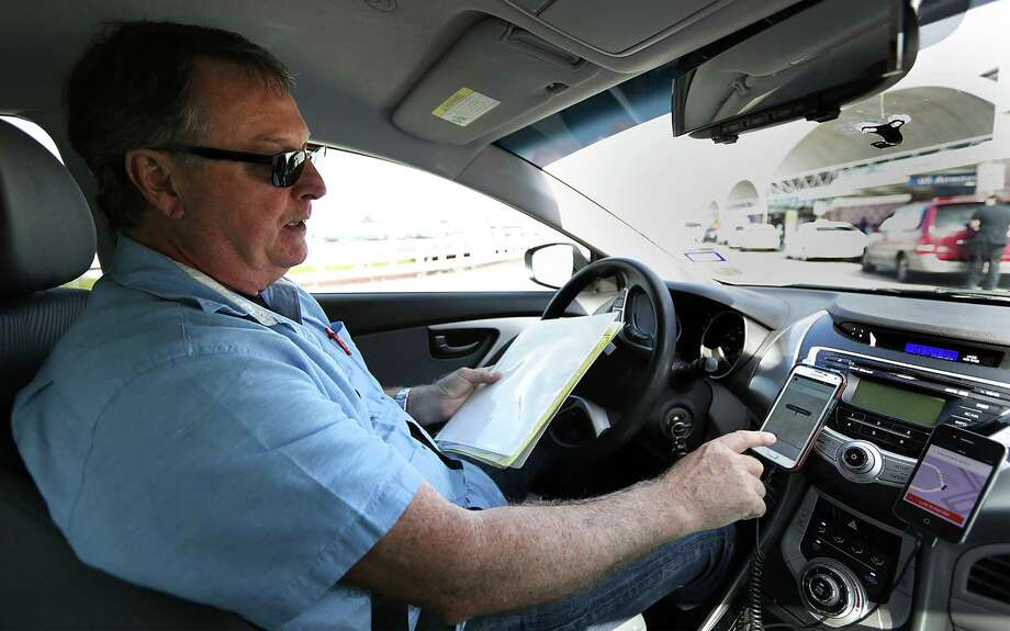 Uber driver Dale Blankenship drives around San Antonio International Airport with a list of arriving flights in the fall of 2014. Photo: Bob Owen /San Antonio Express-News / © 2014 San Antonio Express-News