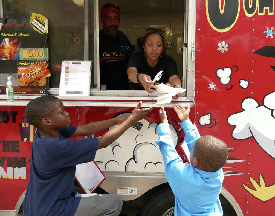 Marlene Parks of the Ooh 'Wee Wings food trailer hands an order of chicken and waffles to Desmond, left, and Phesean Gant during the 2016 Soul Food & Gospel Festival at Maverick Plaza in La Villita on Saturday, May 21, 2016. Soul food sold by vendors included chicken and waffles, hot wings, pork chops and fish sandwiches, ham hocks, black-eyed peas, yams and cornbread. Photo: Billy Calzada, Staff / San Antonio Express-News / San Antonio Express-News