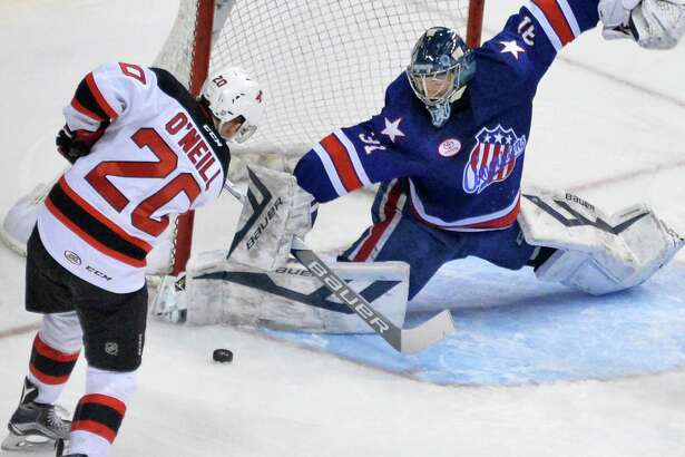 Albany Devils' #20 Brian O.Neill, left, tries a shot against Rochester Americans goalie Nathan Lieuwen during Saturday's game at the Times Union Center Feb. 13, 2016 in Albany, NY.  (John Carl D'Annibale / Times Union)