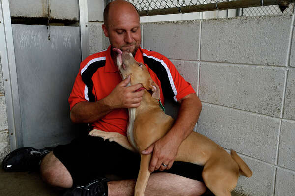 James Everett plays with his newly-adopted dog during the Adoptathon at Beaumont Animal Services on Saturday. By 1:30 p.m., seven animals had been adopted during the event, which also featured food, face painting and a display of Camaros. Photo taken Saturday 5/21/16 Ryan Pelham/The Enterprise