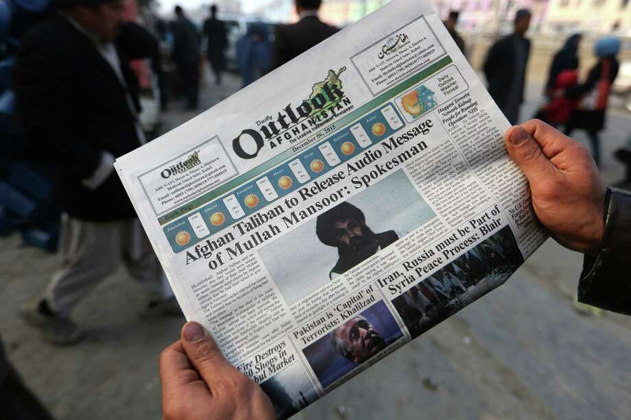 FILE - In this Dec. 6, 2015 file photo, an Afghan man reads a local newspaper with photos of the leader of the Afghan Taliban, Mullah Mansour, in Kabul, Afghanistan.  The Pentagon has announced that the U.S. has conducted an airstrike targeting Taliban leader Mullah Mansour. A U.S. official who wasn't authorized to publicly discuss the operation said Mansour and a second male combatant accompanying him in a vehicle were likely killed.  (AP Photo/Rahmat Gul) Photo: Rahmat Gul, STF / Copyright 2016 The Associated Press. All rights reserved. This material may not be published, broadcast, rewritten or redistribu
