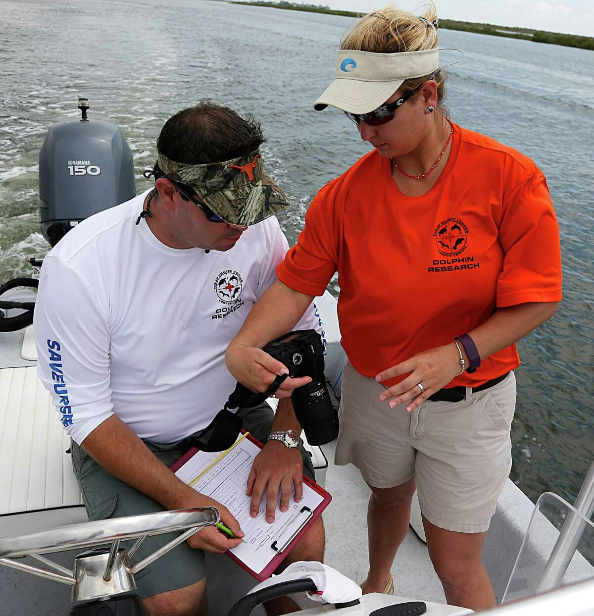 Will McGlaun, left, research director of Texas Sealife Center in Corpus Christi, and volunteer Sara Callender record data from photographs during a dolphin survey on Tuesday in Port Aransas.