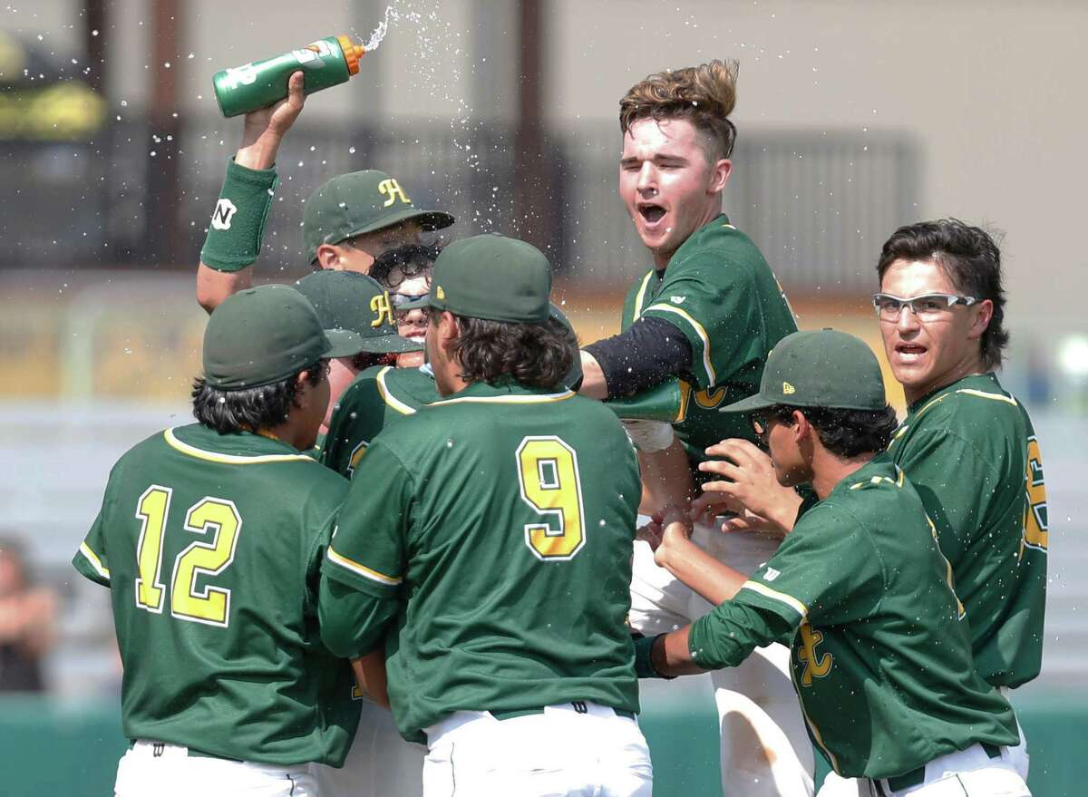 Aaron Arevalos is mobbed by teammate his game-winning hit in the eighth inning against Corpus Christi King in Game 2 of the Class 6A third-round playoff series on May 21, 2016.