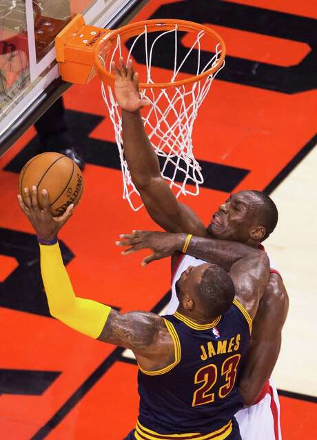 The Raptors' Bismack Biyombo, right, blocks the shot of Cavaliers star LeBron James in the second half of Saturday's game. Biyombo had four blocks, 26 rebounds and seven points in Toronto's victory. Photo: Nathan Denette, SUB / The Canadian Press
