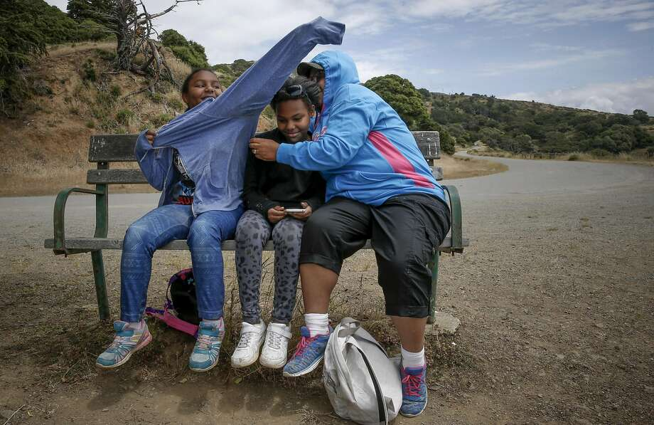 Robbin Summerall and daughters Tahlia, 10, (left) and Milan, 11 huddle together to keep warm. Photo: Michael Macor, The Chronicle