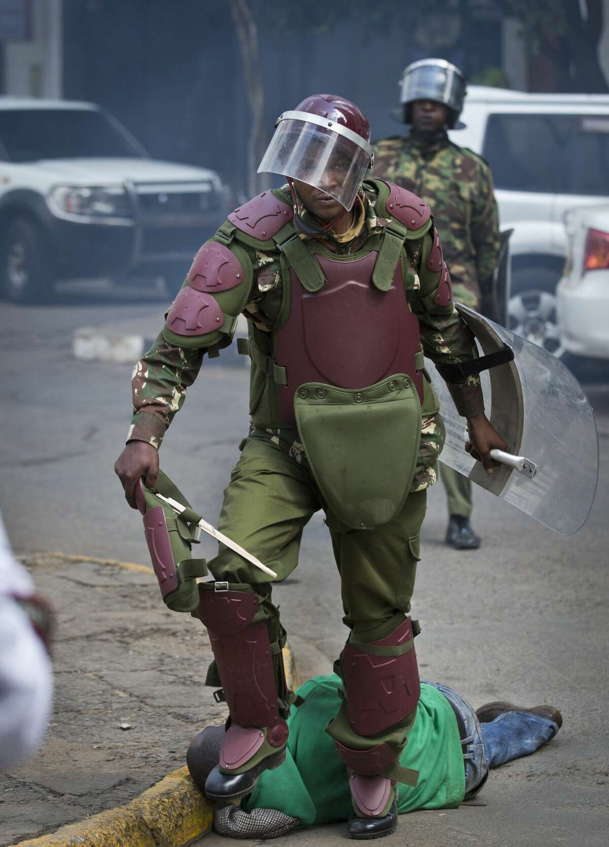 A Kenyan riot policeman walks away after repeatedly kicking a protester, as he lies in the street after tripping over while trying to flee from them, during a protest in downtown Nairobi, Kenya Monday, May 16, 2016. Kenyan police have tear-gassed and beaten opposition supporters during a protest demanding the disbandment of the electoral authority over alleged bias and corruption. (AP Photo/Ben Curtis) AP story: Kenya: Photos of police violence spark international outrage