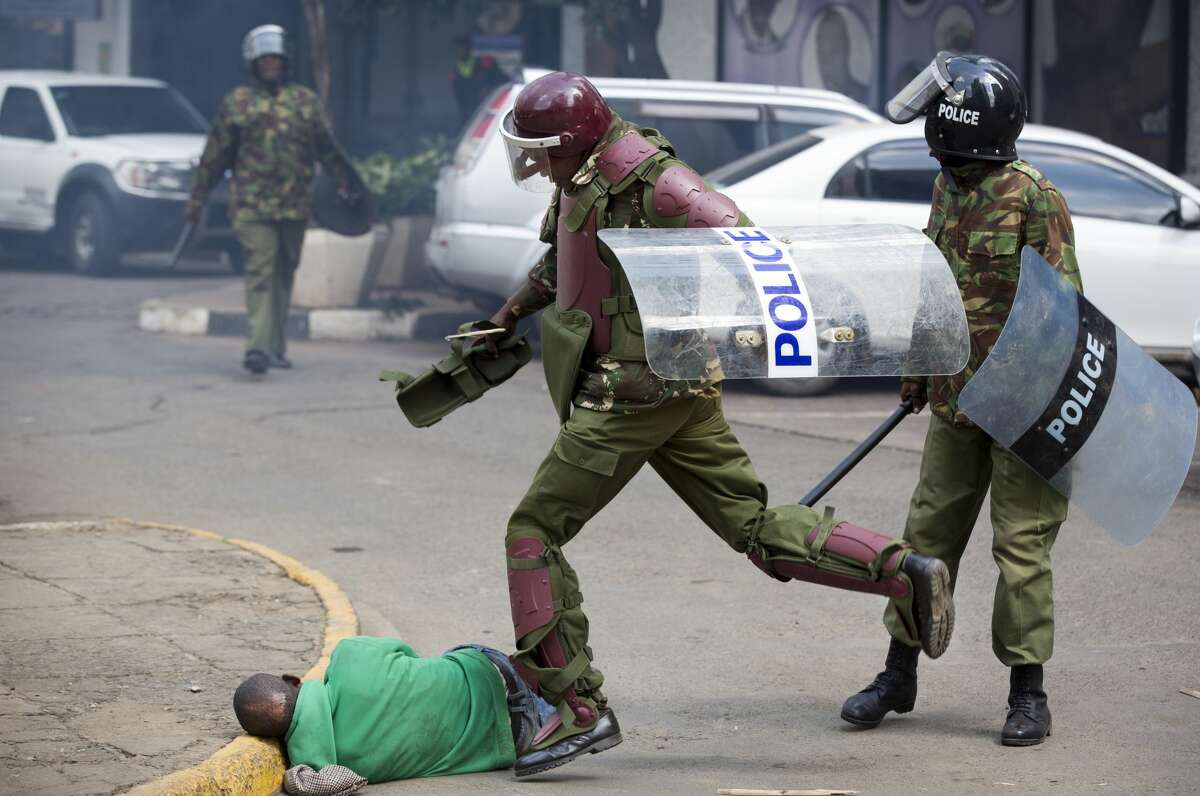 In this Monday, May 16, 2016 file photo, a Kenyan riot policeman repeatedly kicks a protester as he lies in the street after falling down while trying to flee from them, during a protest in downtown Nairobi, Kenya. In an incident that has stirred anger and condemnation across Kenya, a policeman is seen beating and kicking one protester who had fallen on a road curb, while the U.S. and human rights activists have condemned violence by Kenyan police at the opposition protest for election reforms. (AP Photo/Ben Curtis, File) AP story: Kenya: Photos of police violence spark international outrage
