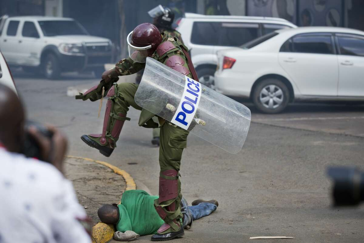 A Kenyan riot policeman repeatedly kicks a protester as he lies in the street after tripping over while trying to flee from them, during a protest in downtown Nairobi, Kenya Monday, May 16, 2016. Kenyan police have tear-gassed and beaten opposition supporters during a protest demanding the disbandment of the electoral authority over alleged bias and corruption. (AP Photo/Ben Curtis) AP story: Kenya: Photos of police violence spark international outrage