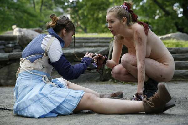 "EDS NOTE: NUDITY - Kara Lynn, left, as Ferdinand, and Marisa Roper, as Miranda perform at Summit Rock in Central Park during the Outdoor Co-Ed Topless Pulp Fiction theater company's production of Shakespeare's ""The Tempest,"" Thursday, May 19, 2016, in New York. An all-female cast of 13 actors, dancers, and musicians perform in this a ""stripped-down"" production which has been for shorter running time. The production uses semi- and full-nudity to celebrate body freedom and free expression and to dramatize the conflict between the visitors to Prospero's island and its inhabitants. (AP Photo/Kathy Willens)"
