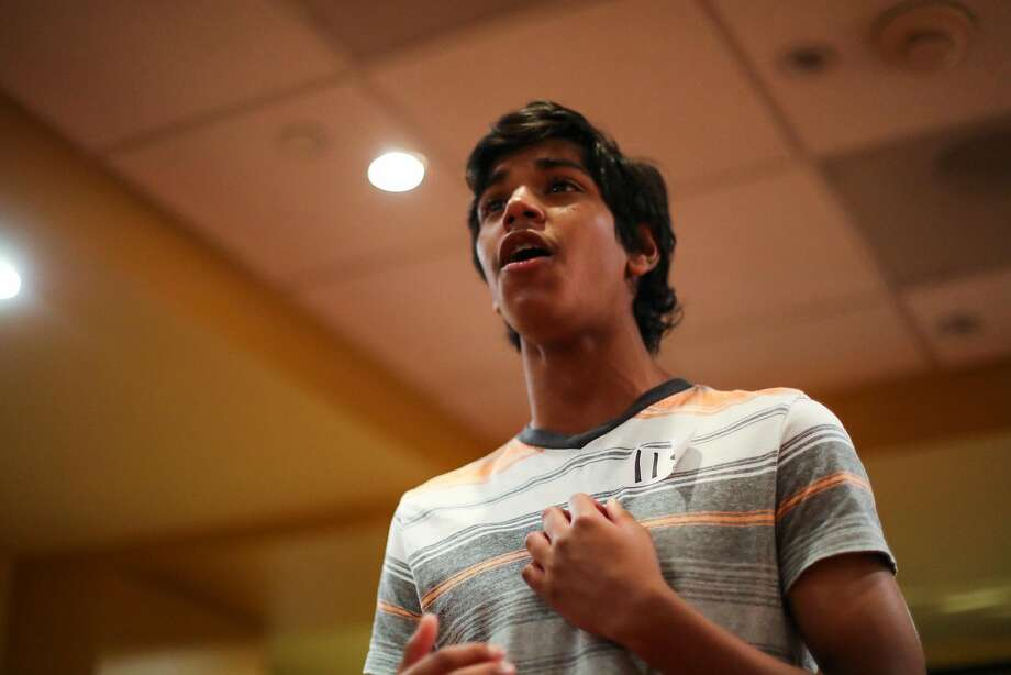 """Dinesh, above, 13, sings for directors during an audition for """"Broadway Movie Musical,"""" while Annelise Hall, left, 8, plays on a phone with her mother, Melissa Hall, as she waits to try out. Photo: Gabrielle Lurie, Special To The Chronicle"""