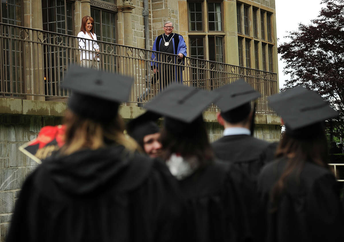 Fairfield University President Jeffrey P. von Arx, S.J. welcomes graduates from a balcony at Bellarmine Hall as they march in to the Fairfield University graduation in Fairfield, Conn. on Sunday, May 22, 2016.