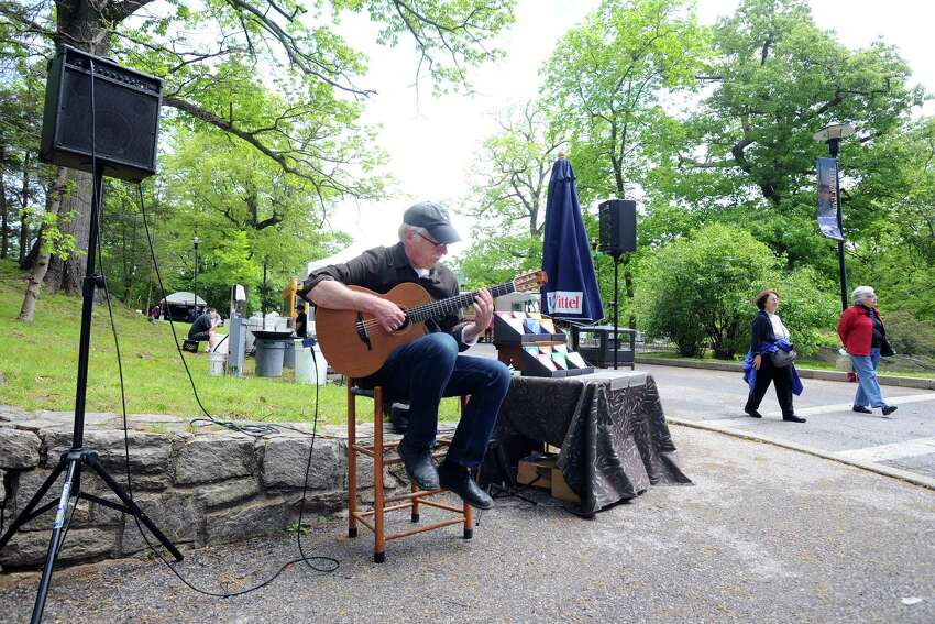 Ed Wright plays the acoustic guitar during the 31st annual outdoor crafts festival at the Bruce Museum in Greenwich, Conn. on Sunday, May 22, 2016.