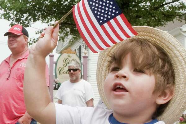 Two-year-old Tristan Alworth of Bethel waves at the marchers during the Bethel Memorial Day Parade on Greenwood Avenue. Sunday, May 22, 2016