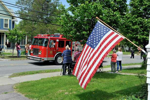 Background from left to right, former Mayor of Altamont, Jim Caruso, his wife Rosemary, Kelly Whalen and Cindy Kaczmarek wave to the driver of a fire truck as they watched the Altamont Memorial Day Parade on Sunday, May 22, 2016, in Altamont, N.Y.  (Paul Buckowski / Times Union)