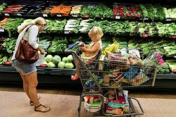 Anne Goss buys produce with her 18-month-old daughter, Stella, at the Kroger Store on Buffalo Speedway on  Friday, May 20, 2016, in Houston. The store is one of Houston Chronicle's top 100.