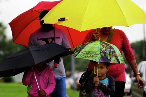 Makayla Monroe, 4, peeks out from under her umbrella as she walks through the rain with her family Monday, May 16, 2016 in Houston. The rain is expected to continue through the week.