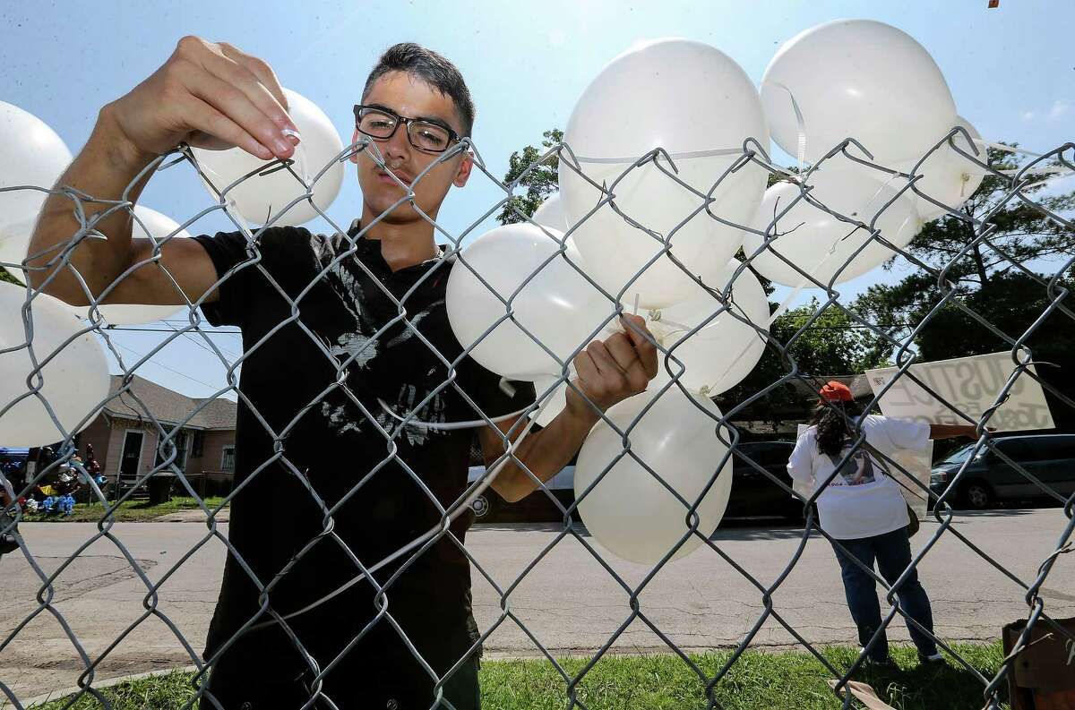 Oziel (cq) Castillo, 14, ties balloons onto a fence for an upcoming event for Josue Flores while Priscilla Gonzales holds signs for Justice for the 11-year-old who was murdered walking home from school. Photos at a memorial on Fulton Street for Josue Flores on Sunday, May 22, 2016, in Houston. ( Elizabeth Conley / Houston Chronicle )