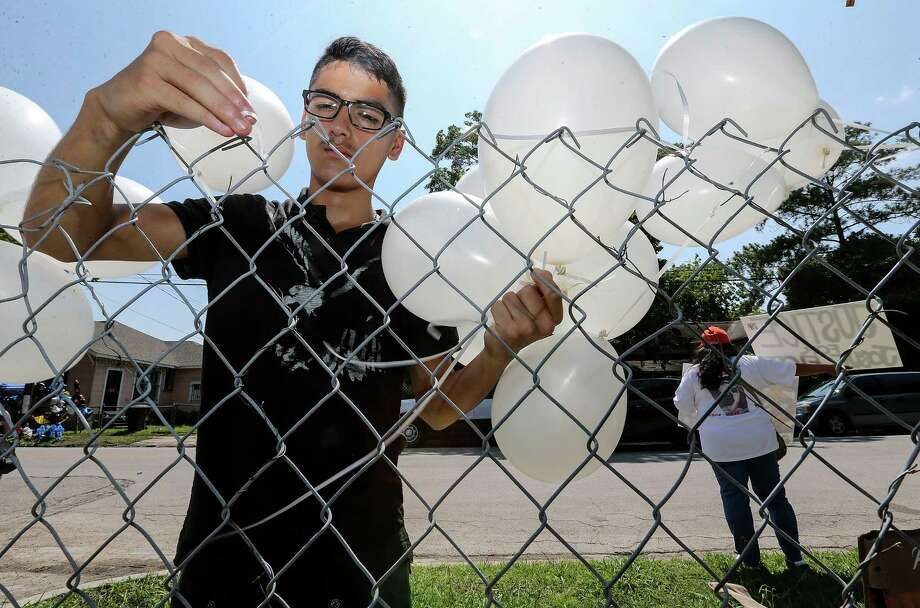 Oziel (cq) Castillo, 14,  ties balloons onto a fence for an upcoming event for Josue Flores while Priscilla Gonzales holds signs for Justice for the 11-year-old who was murdered walking home from school.  Photos at a memorial on Fulton Street for Josue Flores on Sunday, May 22, 2016, in Houston. ( Elizabeth Conley / Houston Chronicle ) Photo: Elizabeth Conley, Staff / © 2016 Houston Chronicle