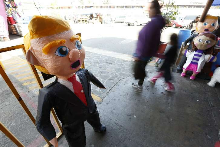 """People pass a pinata in the image of Republican presidential candidate Donald Trump Wednesday, March 2, 2016, in Tijuana, Mexico. Former Mexican President Vicente Fox on Wednesday stood by his comparison of Donald Trump to Adolf Hitler, saying the Republican presidential front-runner �believes in the white supremacy.� Fox is calling on Americans to �wake up� from �this Republican nightmare.� He made the remarks Wednesday in an interview taped for Fox News Channel�s �Hannity.� Trump has angered many Mexicans for his campaign rhetoric denigrating some immigrants as """"rapists"""" who bring crime and drugs to the United States, and his promise to build a wall along the entire US-Mexico border.  (AP Photo/Gregory Bull)"""