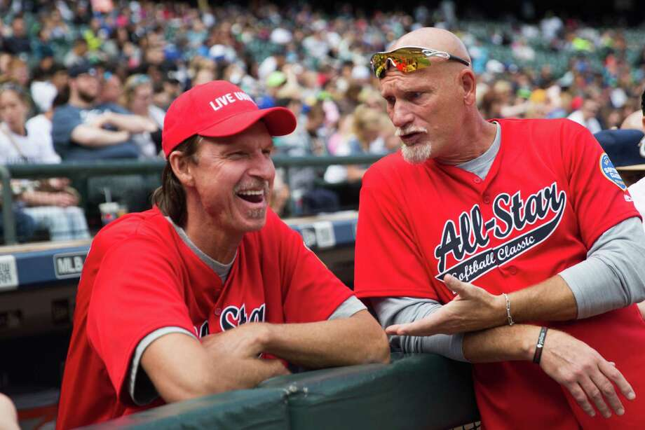 Former Mariners Randy Johnson and Jay Buhner chat in the dugout during the All Star Softball Classic to benefit United Way King County, at Safeco Field, Sunday, May 22, 2016. Photo: GRANT HINDSLEY, SEATTLEPI.COM / SEATTLEPI.COM