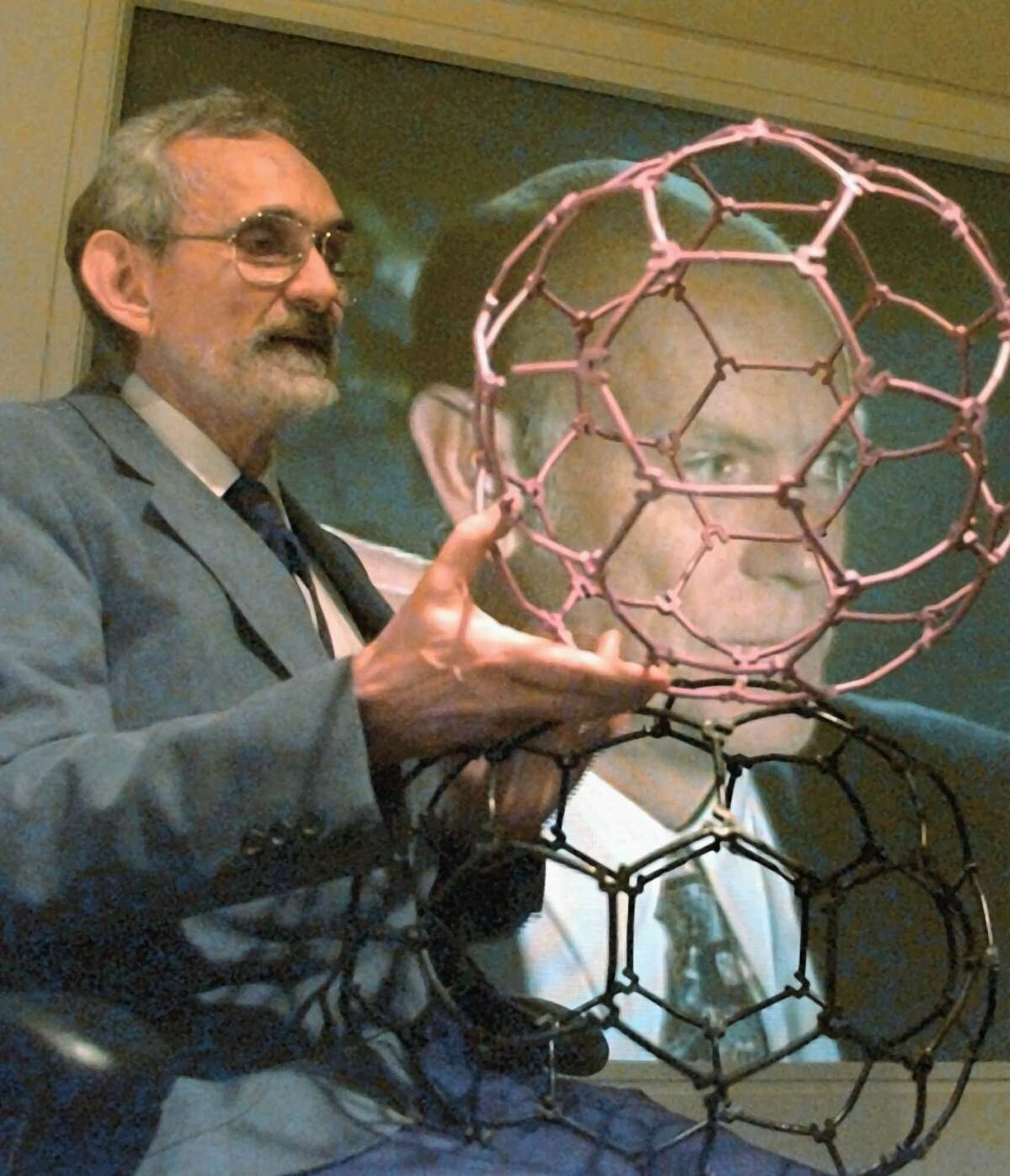 Robert Curl, left, holds plastic molecule models as he talks about the discoveries that earned him the Nobel Prize in Chemistry Wednesday, Oct. 9, 1996, at Rice University in Houston. Co-winner Richard Smalley appears on the television screen behind Curl from Connecticut. The pair, who will share the prize with Harry Kroto of the University of Sussex in Brighton, England, were awarded for their 1985 discovery of a family of soccer ball-shaped carbon molecules known unofficially as ``buckyballs'' and officially as fullerenes, the unusual molecules were named for R. Buckminster Fuller because their structure resembles his famed geodesic domes. (AP Photo/Pat Sullivan)