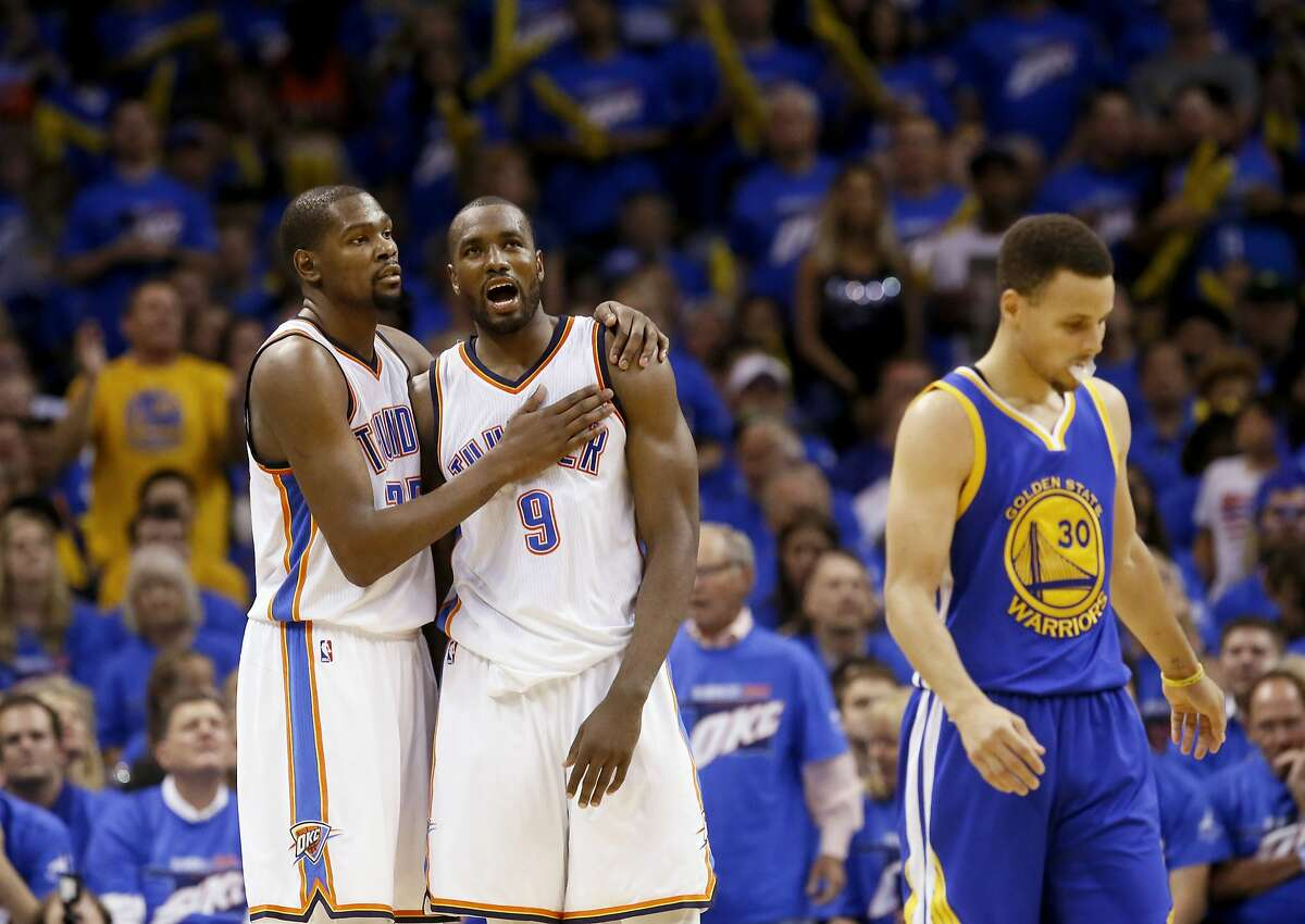 Oklahoma City Thunder forward Kevin Durant (35) and forward Serge Ibaka (9) embrace as Golden State Warriors guard Stephen Curry (30) walks away during the second half in Game 3 of the NBA basketball Western Conference finals in Oklahoma City, Sunday, May 22, 2016.