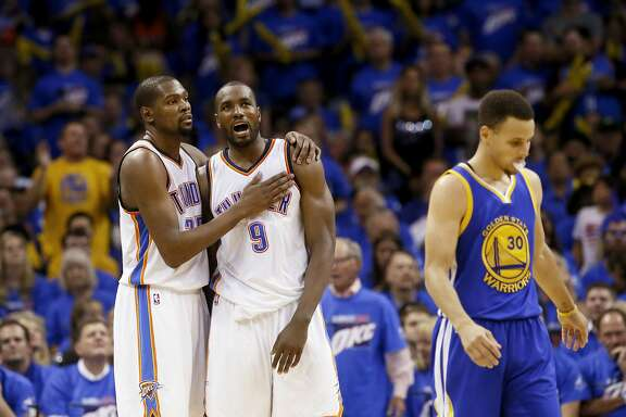 Oklahoma City Thunder forward Kevin Durant (35) and forward Serge Ibaka (9) embrace as Golden State Warriors guard Stephen Curry (30) walks away during the second half in Game 3 of the NBA basketball Western Conference finals  in Oklahoma City, Sunday, May 22, 2016. (AP Photo/Sue Ogrocki)