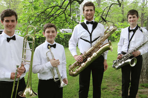 Brass instrumentalists Matt Vogt, 16; Kevin Tzanetis, 13; John Bookas, 17, and Aidan Jacobson, 13, prepare for the performance by the Greater Bridgeport Youth Orchestras on the Great Lawn of the Pequot Library.