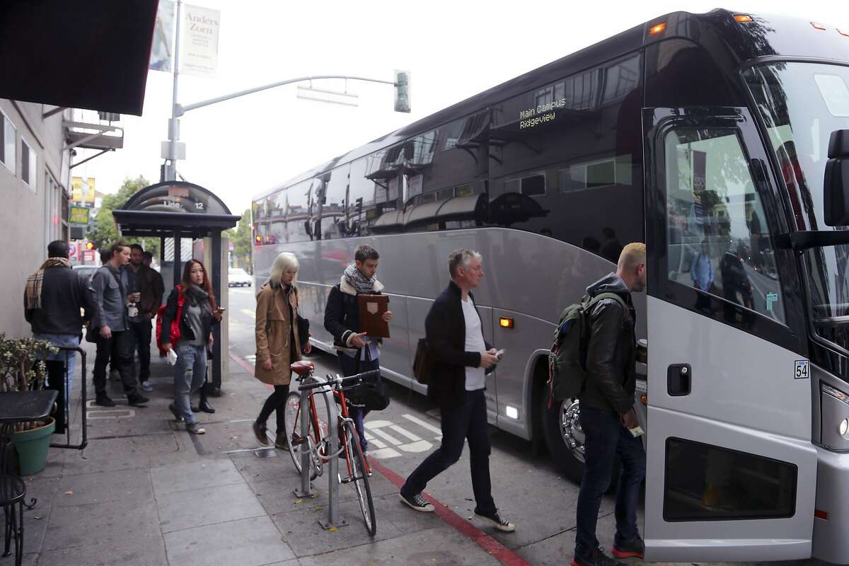 A shuttle bus bound for Silicon Valley offices more than 40 miles away picks up riders in the heart of San Francisco's Mission neighborhood, Jan. 28, 2014. The shuttle buses catering to employees of Apple, Google, Facebook and others have become a a target of ad hoc demonstrations over the gentrification squeezing many less-affluent San Franciscans out of cherished neighborhoods. (Jim Wilson/The New York Times)