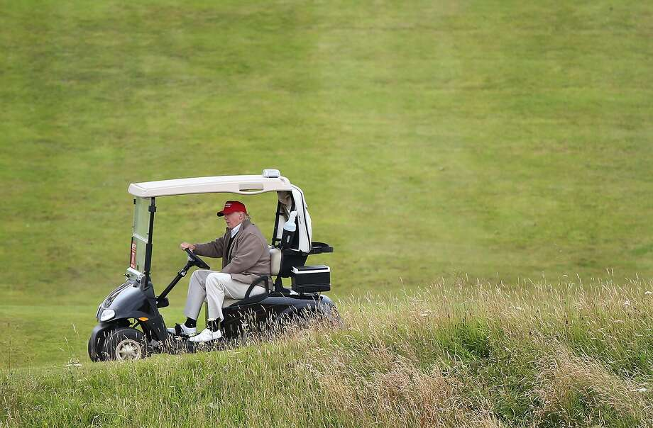 Pictured in a file photo, President Donald Trump drives his golf buggy during the second day of the Women's British Open golf championship on the Turnberry golf course in Turnberry, Scotland. Trump wants to build another huge wall, this time to keep out the rising seas threatening to swamp his luxury golf resort in Ireland. Photo: Scott Heppell, Associated Press