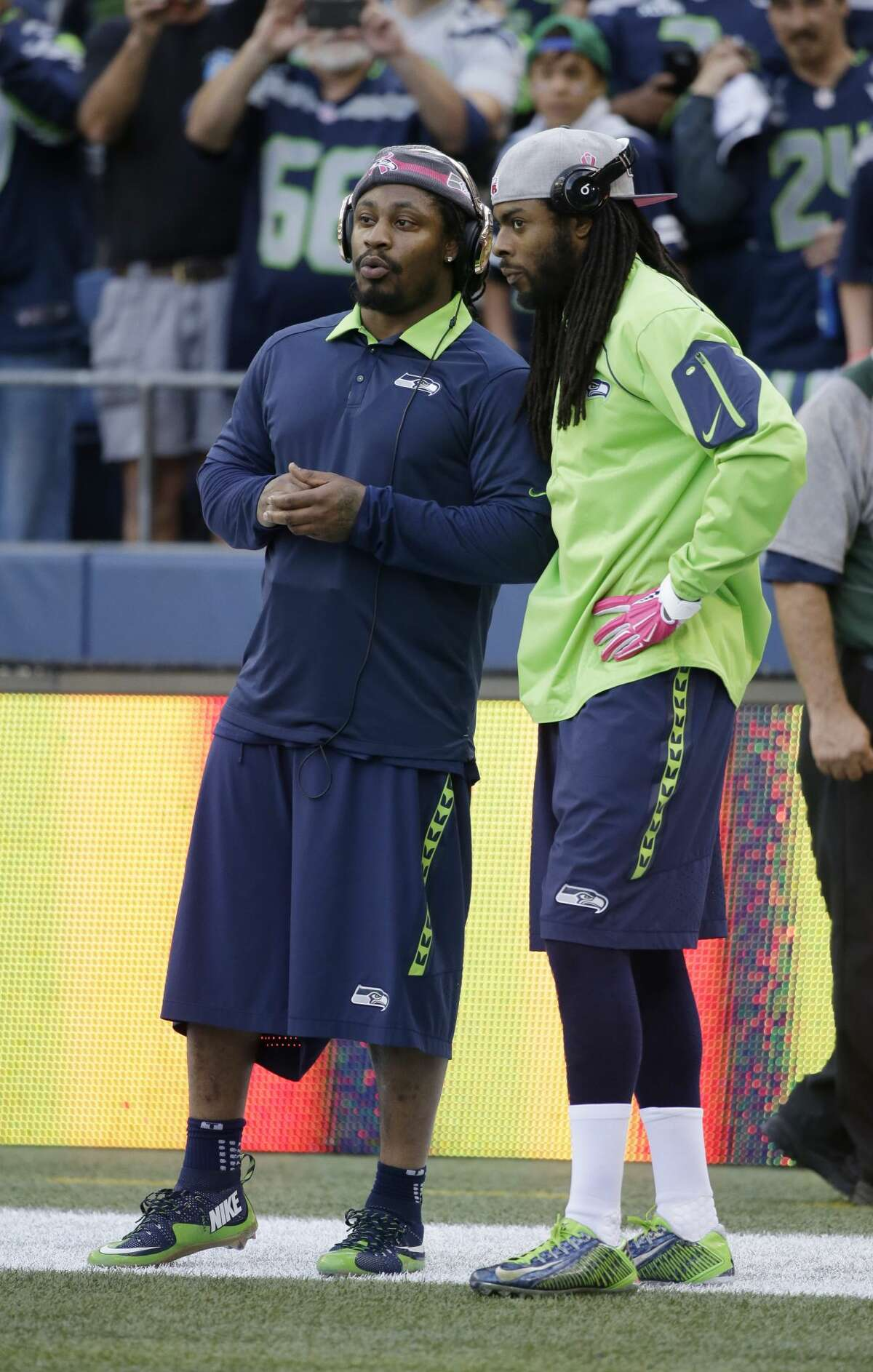 Seattle Seahawks running back Marshawn Lynch, right, greets teammate Richard Sherman, left, during warmups before an NFL football game against the Detroit Lions, Monday, Oct. 5, 2015, in Seattle as they wear pink hats and gloves for breast cancer awareness. (AP Photo/Elaine Thompson)