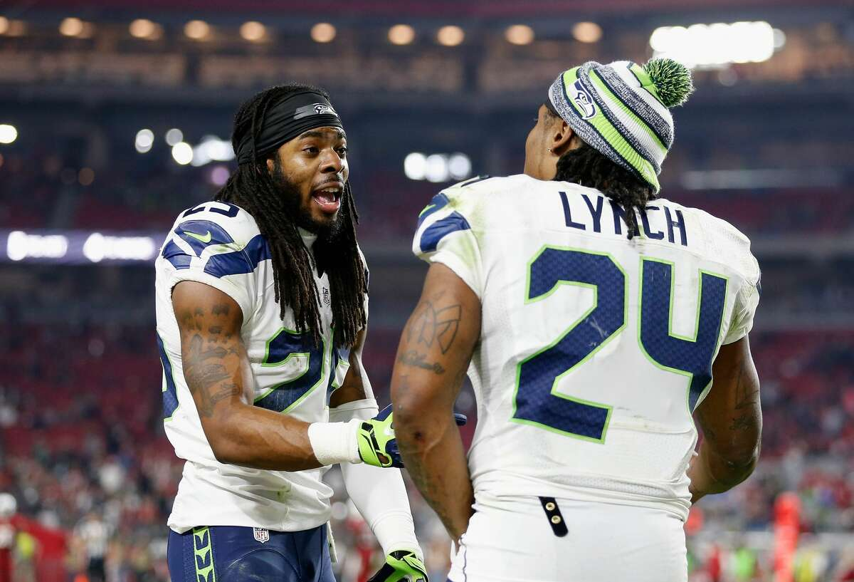 Cornerback Richard Sherman of the Seattle Seahawks talks with running back Marshawn Lynch during the NFL game against the Arizona Cardinals at the University of Phoenix Stadium on December 21, 2014 in Glendale, Arizona. (Photo by Christian Petersen/Getty Images)
