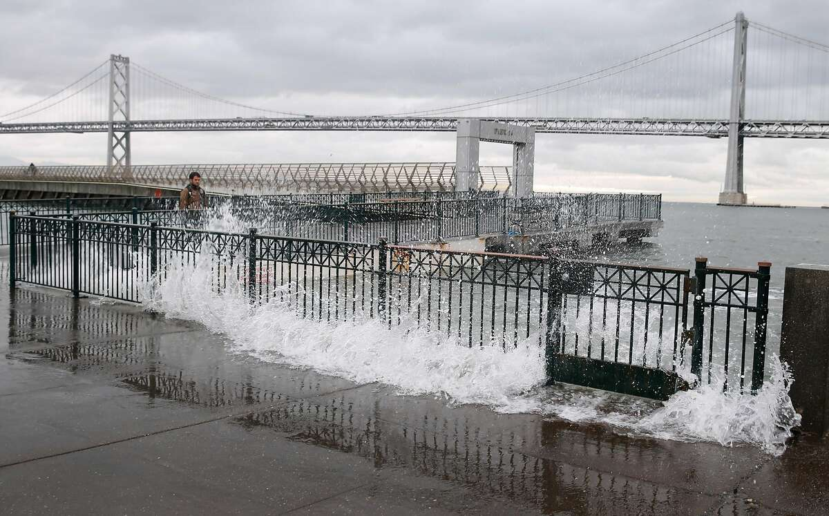 Water from the bay crashes onto the sidewalk at Pier 14 along the Embarcadero at high tide in San Francisco, Calif. in this file photo from Tuesday, Nov. 24, 2015. King tide conditions are causing higher than usual water levels.