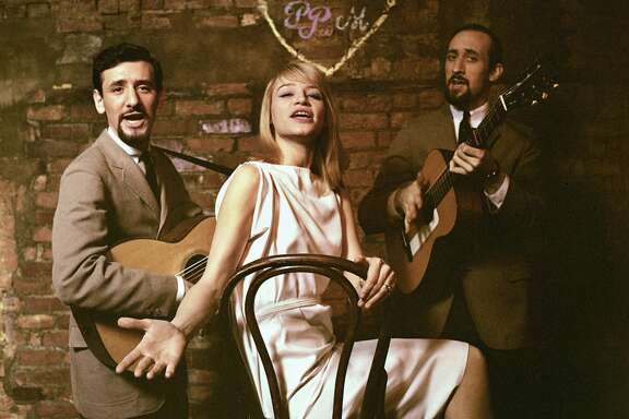 "Peter Yarrow, Mary Travers, and Noel ""Paul"" Stookey of Peter, Paul and Mary pose for alternative shots for the cover of their first, eponymously-titled album at The Bitter End in 1962 in Greenwich Village, New York.  (Photo by Michael Ochs Archives/Getty Images)"