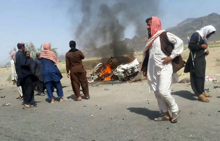 This photograph taken on May 21, 2016 shows Pakistani local residents gathering around a destroyed vehicle hit by a drone strike in which Afghan Taliban Chief Mullah Akhtar Mansour was believed to be travelling in the remote town of Ahmad Wal in Balochistan, around 160 kilometres west of Quetta. Afghan authorities scrambled May 22 to confirm the fate of Taliban leader Mullah Akhtar Mansour after US officials said he was likely killed in drone strikes -- a potential blow to the resurgent militant movement.  / AFP PHOTO / --/AFP/Getty Images