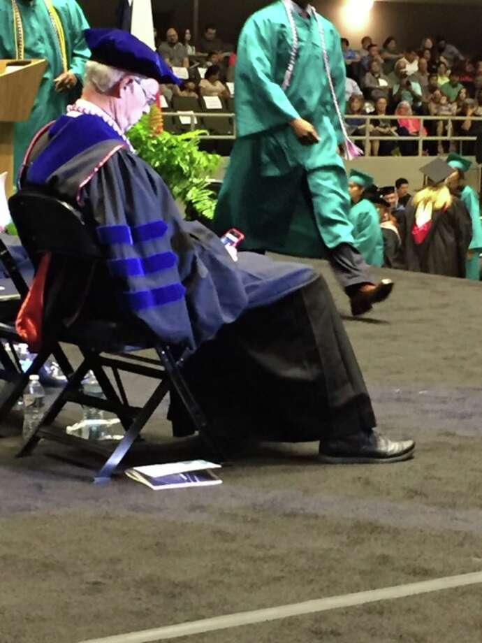 Alamo Colleges Chancellor Bruce Leslie is shown on his phone during Palo Alto College's commencement ceremony on May 21, 2016 at Freeman Coliseum. Photo: Courtesy/Tony Villanueva