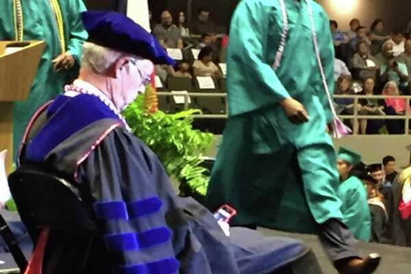 Alamo Colleges Chancellor Bruce Leslie is shown on his phone during Palo Alto College's commencement ceremony on May 21, 2016 at Freeman Coliseum.