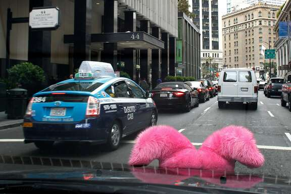 The pink moustache attached to the front grille of Yev Kaplinesky's car flips up while he transports passengers using the Lyft car service in San Francisco, Calif. on Wednesday, Sept. 5, 2012.